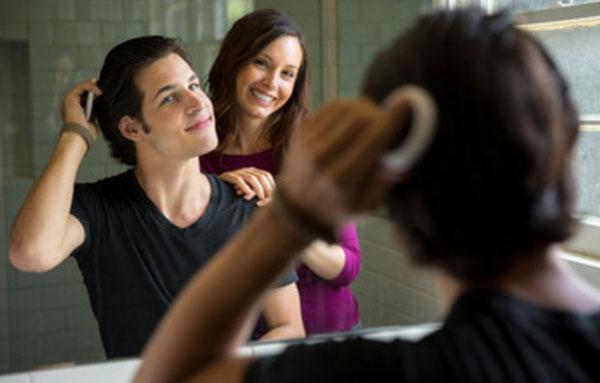 Мужчина причесывается перед зеркалом рядом стоит женщина и улыбается