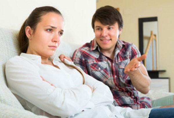 Девушка с парнем сидит на диване. Она игнорирует то, что он говорит, обижена