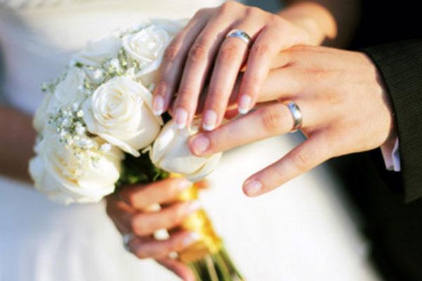 Свадебный букет и руки с обручальными кольцами