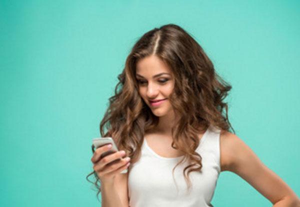 Девушка смотрит на экран телефона и улыбается
