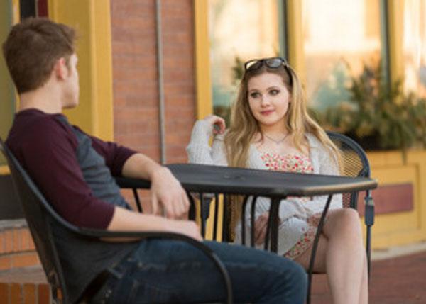 Парень с девушкой сидят за пустым столиком. Оба серьезные