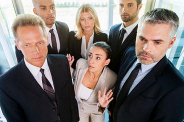 Женщина стоит в окружении людей. Ей страшно