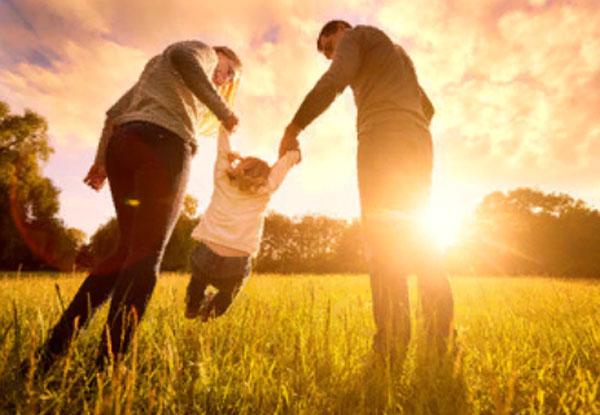Семья с маленьким ребенком на прогулке. На заднем плане ярко светит солнце, находящееся на линии горизонта