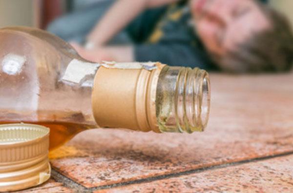 На переднем плане бутылка со спиртным, которая лежит на полу. На заднем - спящий мужчина