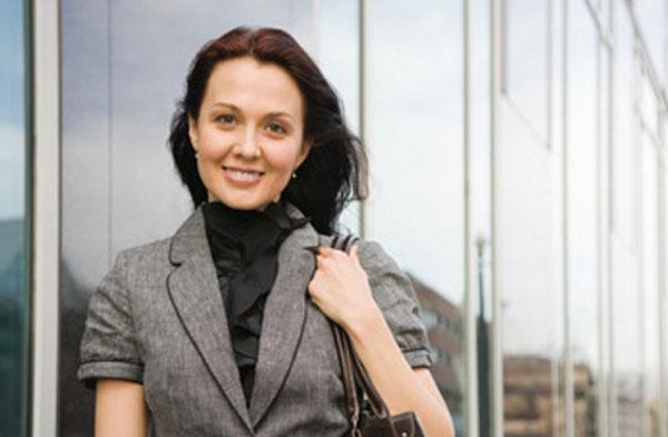 Счастливая девушка стоит возле офисного здания