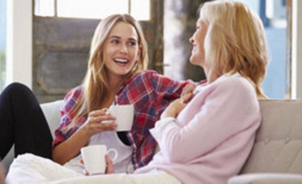 Мама с дочкой весело беседуют за чашкой чая