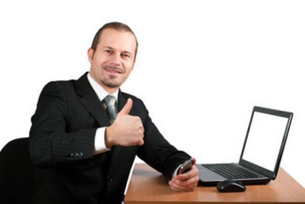 Мужчина за столом с ноутбуком, улыбается, держит палец вверх