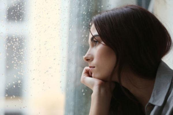 Одинокая женщина смотрит в окно. На улице идет дождь