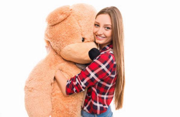 Девушка с большим плюшевым медведем в руках