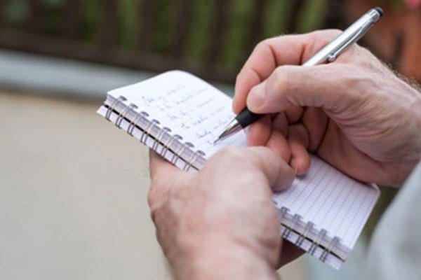 Мужчина пишет какой-то список в блокноте