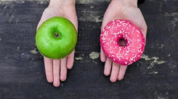 Две ладони. На одной лежит яблоко, на другой - пончик