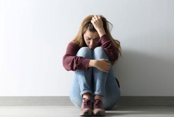 Женщина сидит под стеной. Она очень опечалена