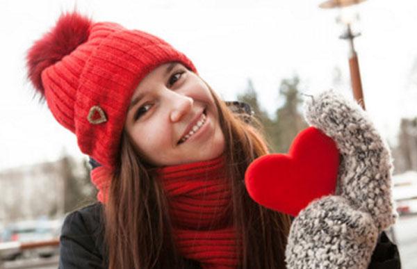 Счастливая девушка в красной шапке с красным шарфом держит в руке красное мягкое сердце