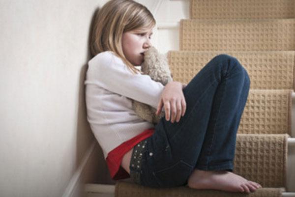 Грустная девочка сидит на ступеньках в обнимку со своей мягкой игрушкой