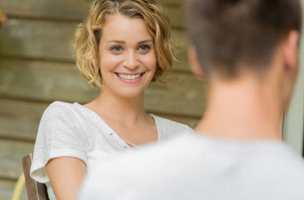 Девушка улыбается и смотрит на парня