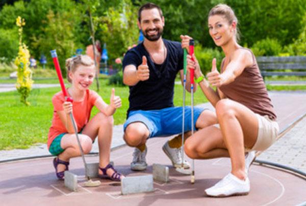 Счастливая семья из трех человек на спортивной площадке