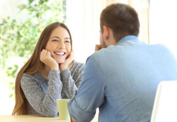 Парень с девушкой сидят за столиком. Она улыбается