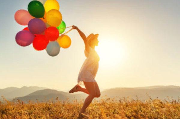 Девушка бежит по траве с воздушными шариками