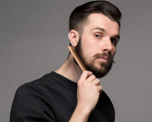 Парень расчесывает свою бороду