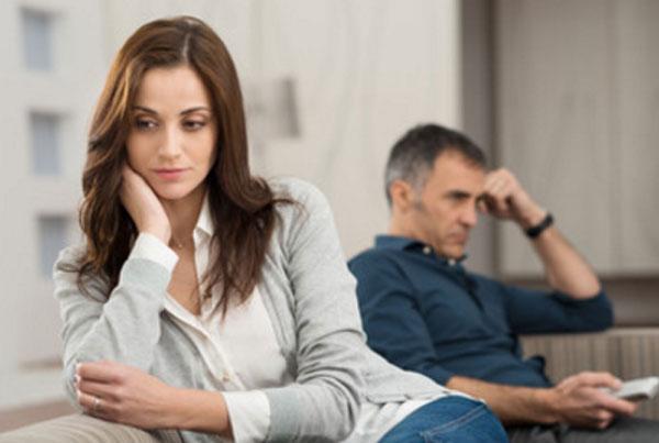 Женщина в задумчивости. На заднем плане ее муж сидит на диване и смотрит телевизор