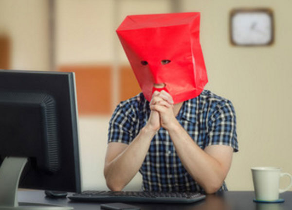 Мужчина сидит перед компьютером в картоном пакете с прорезями для глаз