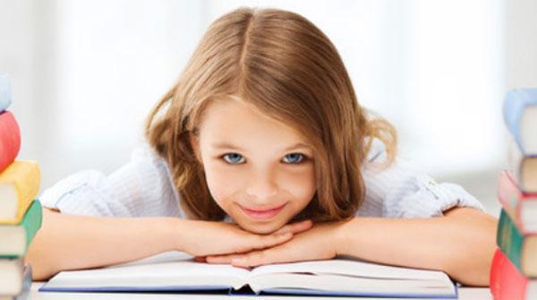 Девочка облокотилась на открытую книгу. Она улыбается