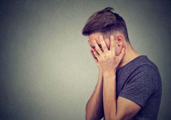 Мужчина руками прячет лицо