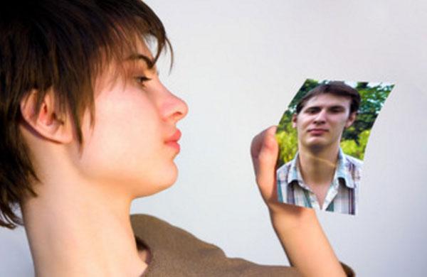 Девушка со слезами на глазах смотрит на фото мужчины