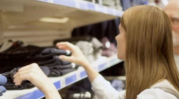 Женщина рассматривает одежду на стеллажах в магазине