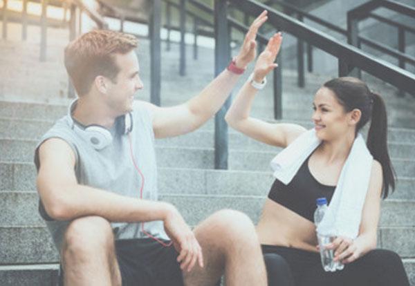 Парень с девушкой в спортивной одежде &quot,дают пять&quot,, сидя на ступеньках