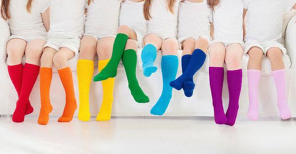 Девочки сидят на диване в носках, у каждой свой цвет