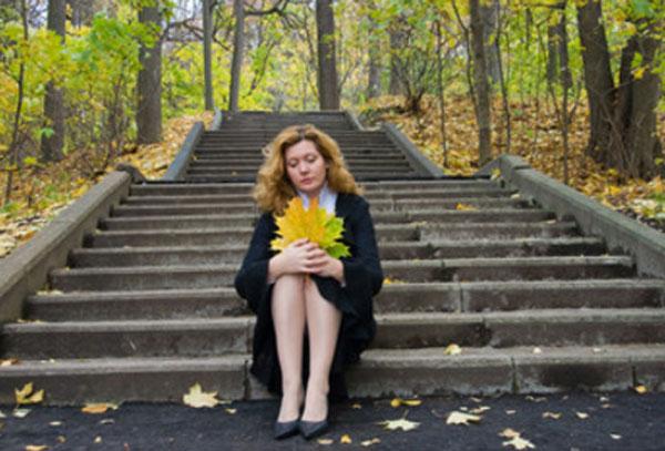 Осень. Женщина сидит на ступеньках с листком в руках