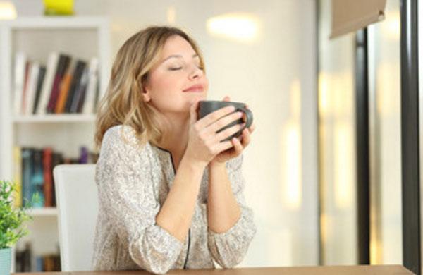 Спокойная умиротворенная женщина с чашкой чая в руках