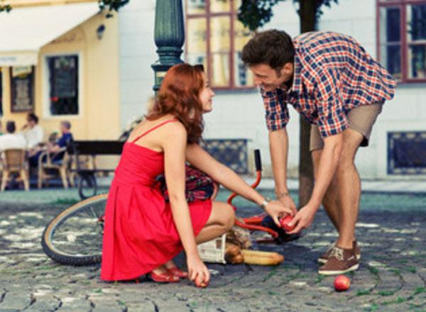 Парень с девушкой собирают продукты, которые рассыпались с перевернутого велосипеда. Одновременно взялись за одно яблоко, смотрят друг другу в глаза