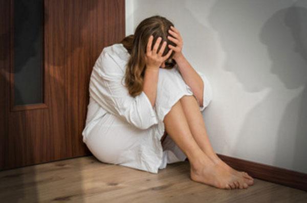 Девушка забилась в угол, прячет лицо, руками держится за голову