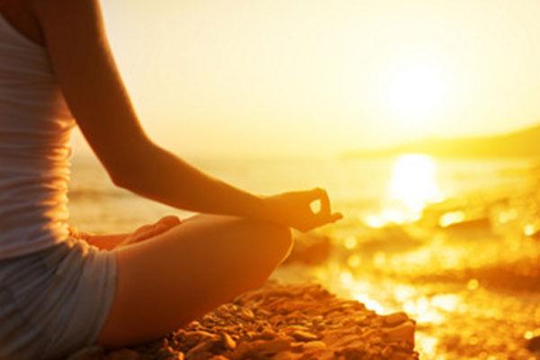 Девушка медитирует, сидя на возвышенности