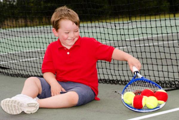 Мальчик сидит на земле возле сетки. Он держит теннисную ракетку, на которой пять мячиков