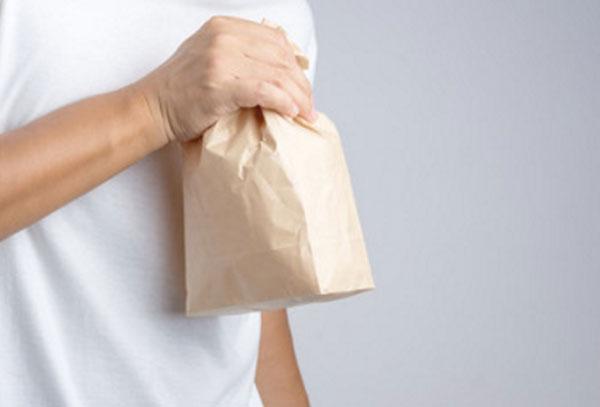 Мужчина держит надутый бумажный пакет