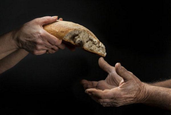 Один человек дают другому половину хлеба