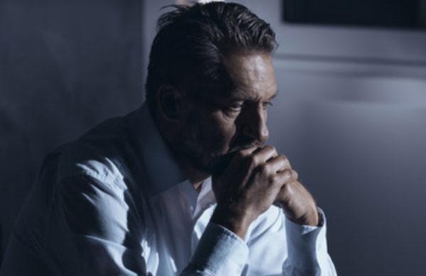Расстроенный мужчина сидит в задумчивости