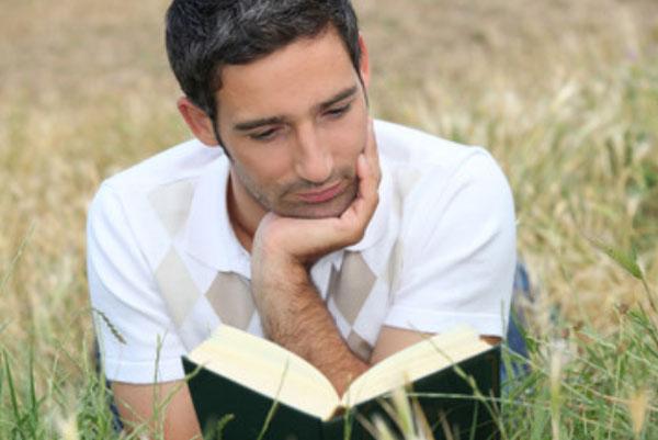 Мужчина читает книгу, лежа на траве