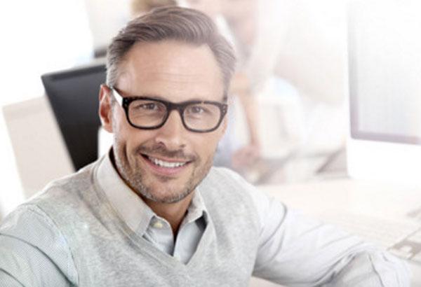 Мужчина в очках на работе. Он улыбается
