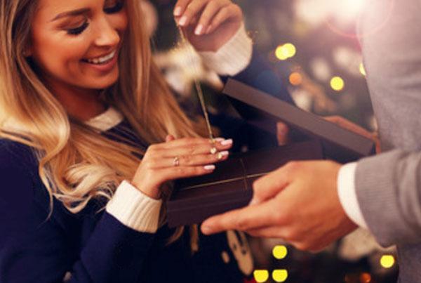 Женщина достает из коробки ювелирное украшение