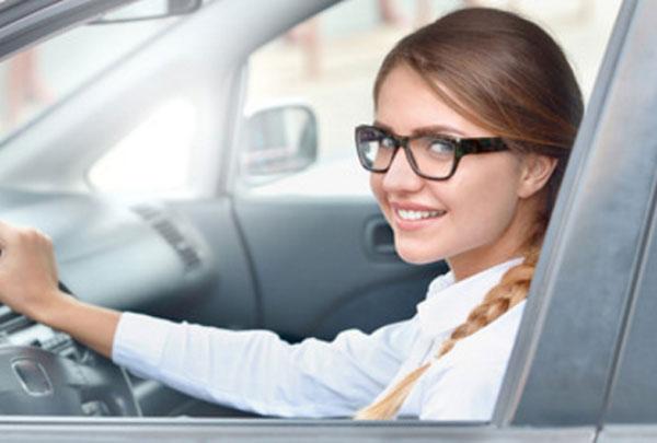 Успешная девушка в очках за рулем машины