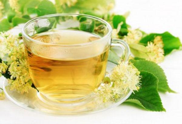 Чашка липового чая. Рядом лежат соцветия липы