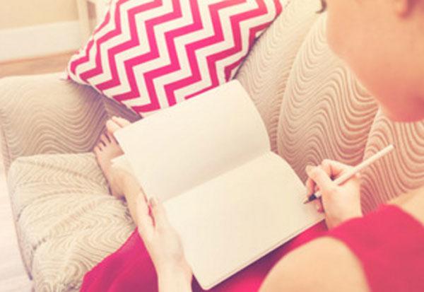 женщина сидит на диване и собирается что-то написать в блокноте