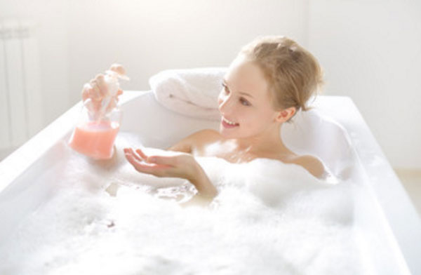 Девушка улыбается, лежит в ванне с пеной