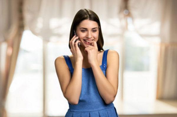 Девушка общается по телефону и загадочно улыбается