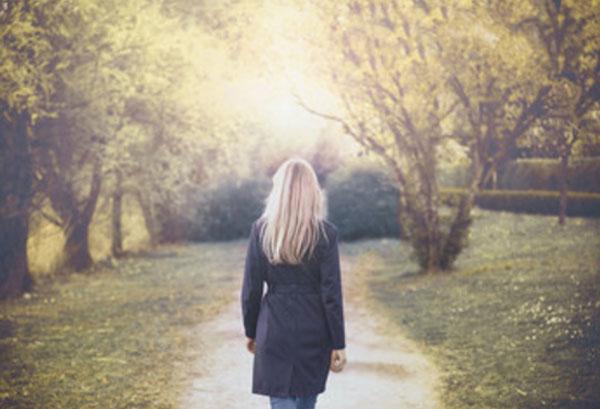 Женщина идет по тропинке. Гуляет по парку