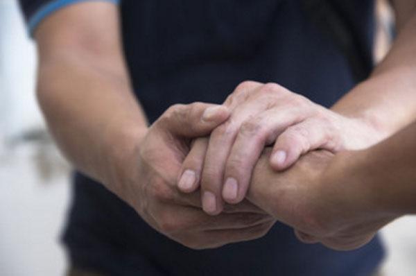 Один человек поддержующе берет руку другого человека